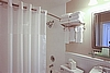 Guest Room Bathroom Amenities featuring curved shower rod, double/head Speakman shower head, shelving, hairdryers, lighting, mirrors and more